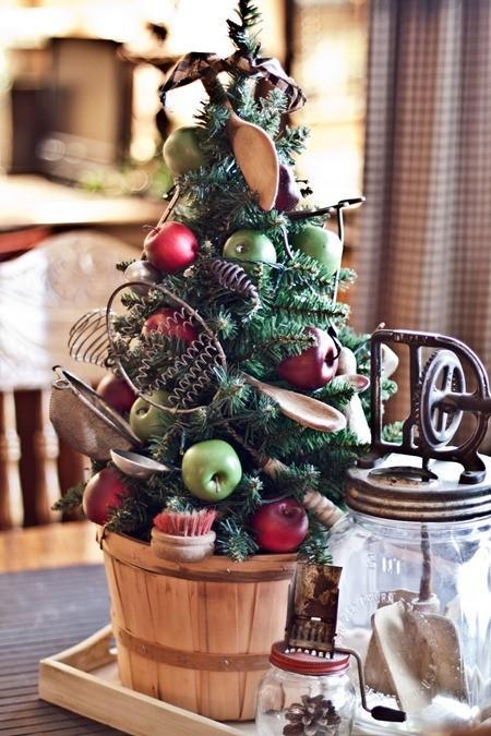 Uma árvore de Natal com colheres de madeira, frutas e utensílios de cozinha em desuso